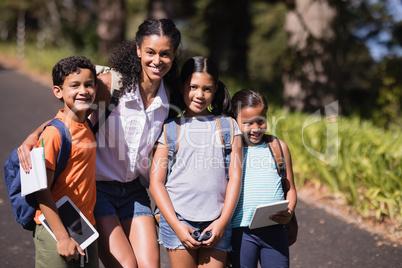 Portrait of happy teacher and children using digital tablets on street