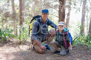 Portrait of father and son kneeling in forest