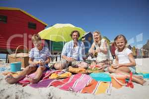 Portrait of happy family sitting together on blanket at beach