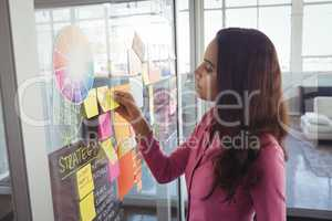Female designer removing adhesive note from glass in creative office