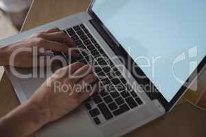 Cropped hands of businesswoman working on laptop