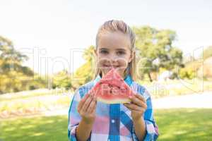 Smiling girl holding watermelon slice in the park