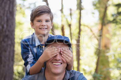 Portrait of boy covering fathers eyes