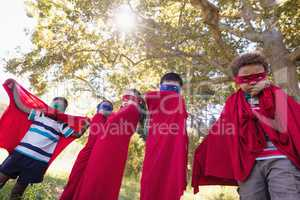 Friends enjoying while wearing superhero costume at campsite