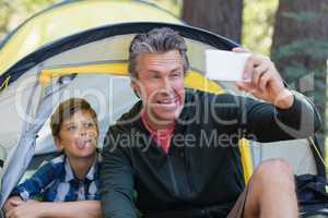 Playful father and son taking selfie in tent