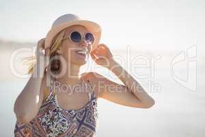 Young woman wearing sunglasses and hat at beach