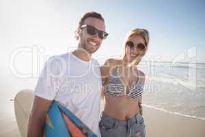 Portrait of happy young couple wearing sunglasses at beach