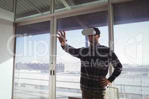 Creative businessman experiencing virtual reality in office