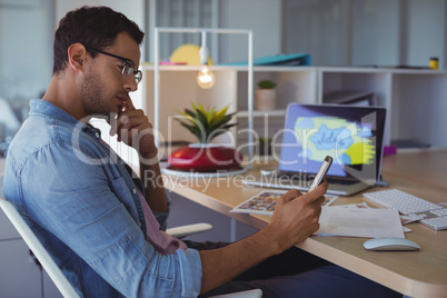 Graphic designer using mobile while sitting in creative office