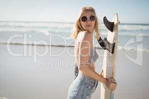 Side view of woman holding surfboard at beach