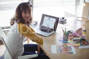 High angle portrait of smiling businesswoman sitting at office desk