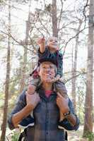 Low angle view of father carrying son on shoulders