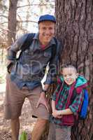 Portrait of happy father and son leaning on tree trunk