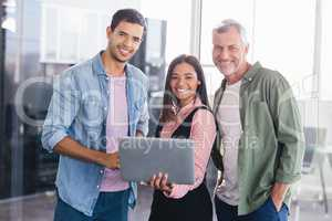 Portrait of smiling business people with laptop
