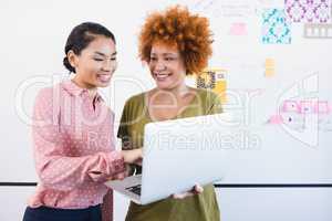 Smiling businesswomen using laptop white standing against whiteboard