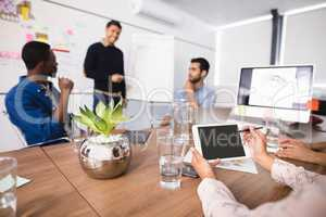 Cropped image of businesswoman using digital tablet while colleagues discussing in meeting room