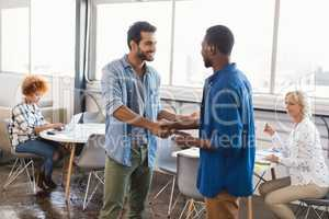 Happy business people shaking hands at creative office