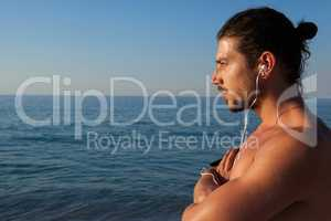 Muscular man looking at sea from beach