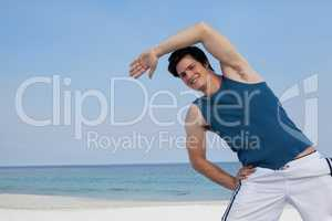 Smiling man doing warm up on beach