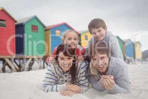 Portrait of happy parents with children lying on sand