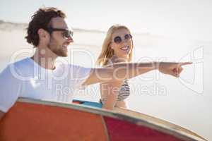 Happy man with woman gesturing while carrying sunrfboard at beach