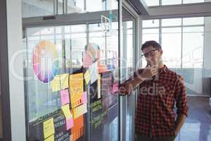 Thoughtful businessman looking at adhesive notes in creative office