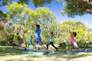 Group of people performing stretching exercise in the park