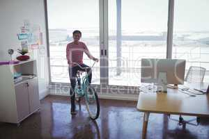 Smiling businesswoman riding bicycle in creative office
