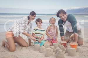 Portrait of happy family making sand castle