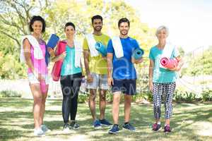 Group of people standing in the park with rolled exercise mats