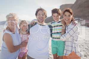 Portrait of multi-generated family embracing at beach