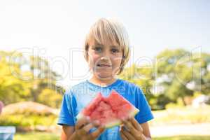 Smiling boy holding watermelon in the park