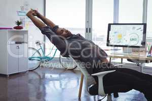 Businessman stretching on chair in creative office