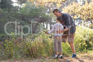 Father teaching boy fishing in forest