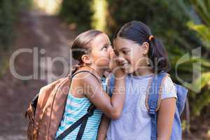 Girl whispering to friend at natural parkland