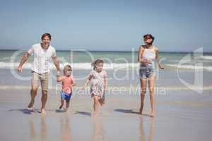 Happy family running on shore at beach