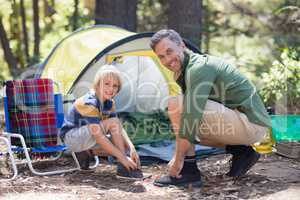 Smiling father and son tying shoelace by tent at campsite