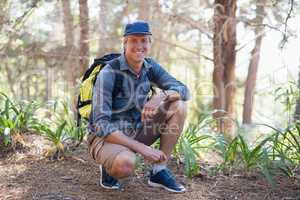 Portrait of hiker kneeling on trail against trees
