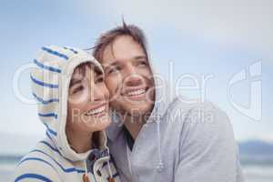 Smiling couple wearing hooded sweater while looking away