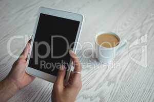 Hands of businesswoman holding holding digital tablet by coffee cup on table