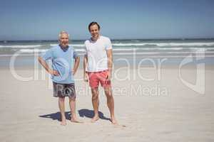 Portrait of man with father standing at beach