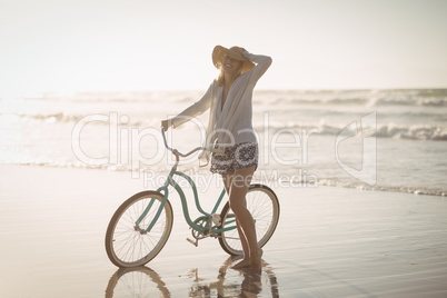 Full length of woman standing by bicycle on shore at beach