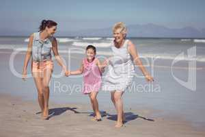 Happy multi-generation family running while holding hands at beach