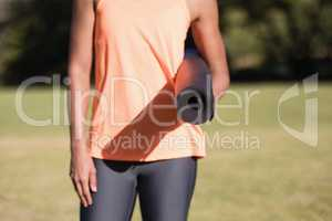 Midsection of woman holding exercise mat