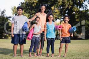 Portrait of children and instructor holding exercise mat