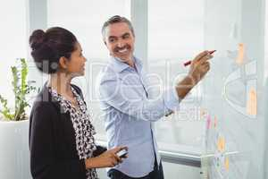 Colleagues discussing over sticky note