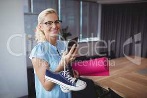 Smiling executive using mobile phone while holding exercise mat and shoes