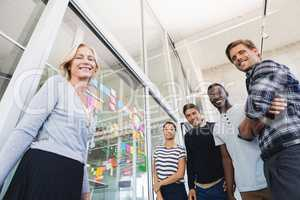 Low angle portrait of business people by plan on glass wall