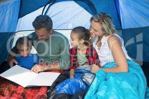Family reading book in the tent
