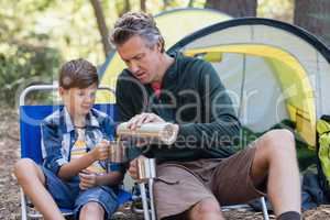 Father pouring drink in cup for son in forest